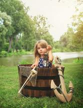 a child in a barrel pretending its a boat