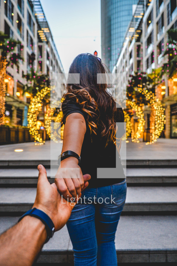 woman leading a man towards a city