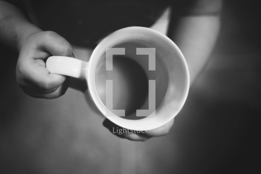 toddler holding an empty mug