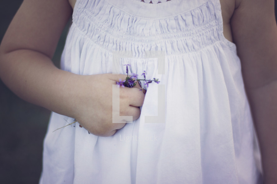 girl holding a tiny purple flower