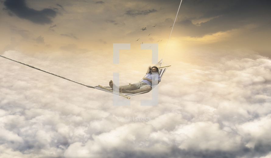 a man in a hammock relaxing above the clouds