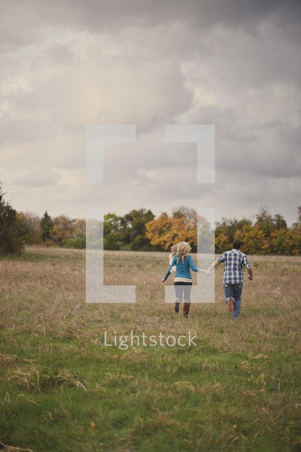 couple running through a field holding hands