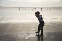 a boy splashing in wet sand on a beach