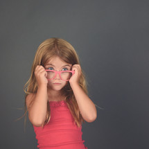 a little girl putting on glasses
