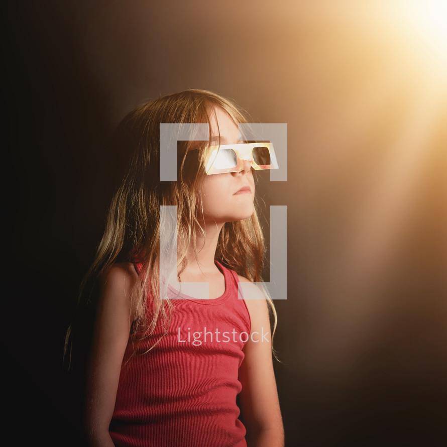 child wearing solar eclipse glasses