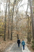 brothers walking down a path in a forest in fall