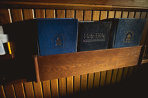 Hymnals and a Bible in the back of a pew