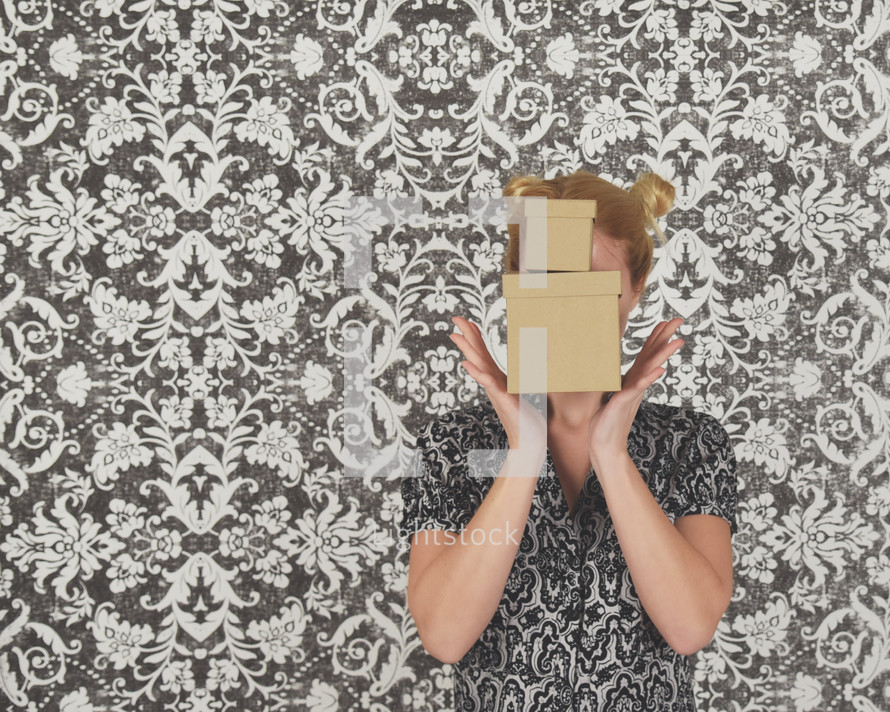 a woman holding gift boxes in front of her face