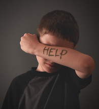 a child with help written on his arm