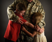a military father hugging his children