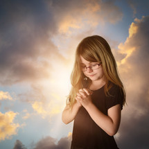 a little girl with glasses praying at sunrise