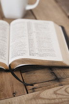 open Bible and coffee mug on a wood table