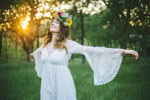 a woman standing in a field with outstretched arms with flowers in her hair