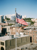 American flag flying above a city