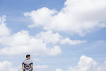 a man standing outdoors thinking with blue skies in background