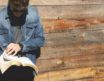 a man reading a Bible in front of a wall of wood