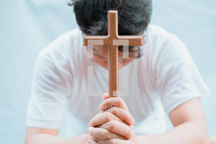 a man holding a wooden cross praying
