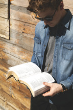 a young man reading a Bible in front of a wall of wood boards