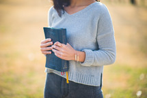 young woman holding a Bible against her chest
