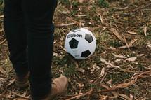 man in boots beside a soccer ball