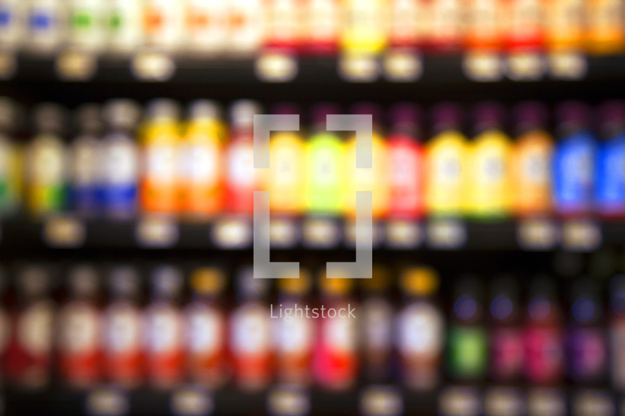 blurry image of juice bottles on a store shelf