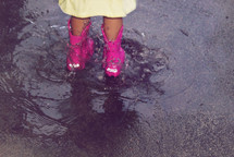 A child wearing pink rain boots standing in a puddle.