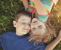 siblings snuggling in the grass