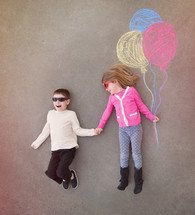 brother and sister holding sidewalk chalk balloons