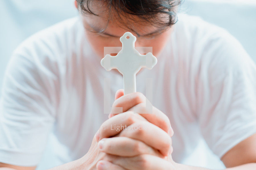 a man with head bowed holding a cross praying