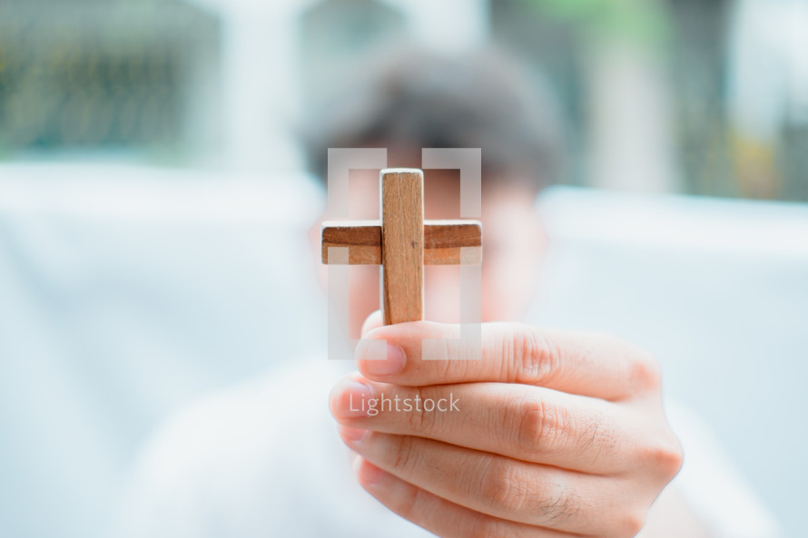 man holding a small wooden cross