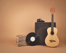 speaker, acoustic guitar, records, and headphones