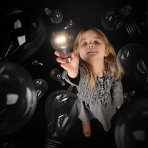 a girl holding up a bright lightbulb