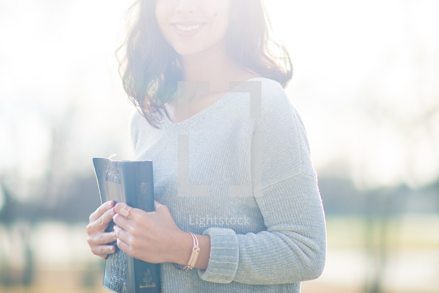 a young woman holding a Bible against her chest