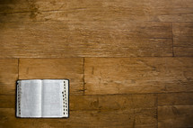 open Bible on a wood floor