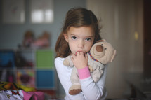 child sucking her fingers holding a teddy bear