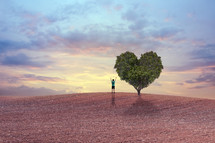 man with raised hands standing next to a heart shaped tree