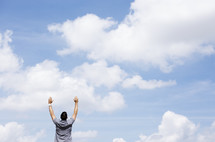 man with raised arms standing outdoors with blue skies as background