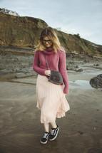 a woman in a skirt walking on a beach