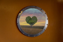 view of a heart shaped tree through a circular window