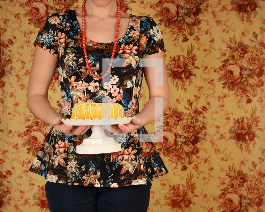 a woman holding a cake