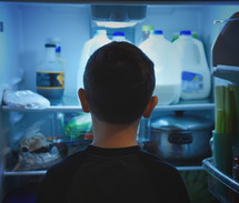 a boy child looking into a refrigerator