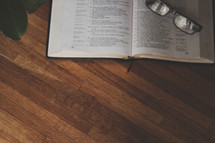 reading glasses on the pages of an open Bible