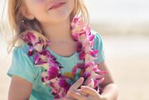 a girl child wearing an Hawaiian Leis