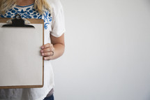 woman holding a blank piece of paper on a clipboard