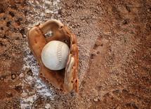 baseball glove and baseball on a baseball diamond