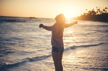 a woman with outstretched arms standing on a beach at sunset