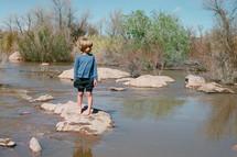 boy standing on a rock in stream