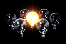 Bright lightbulb among other inactive bulbs