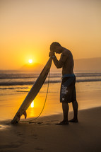 surfer with his head bowed in prayer
