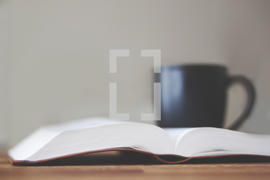 open Bible on a table with a coffee cup
